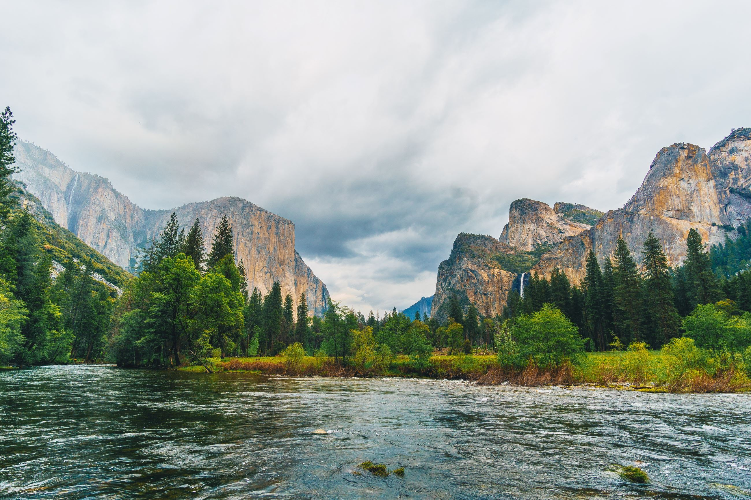 An image of the Yosemite Valley with the Merced River in the middle, El Capitan on the left and Half