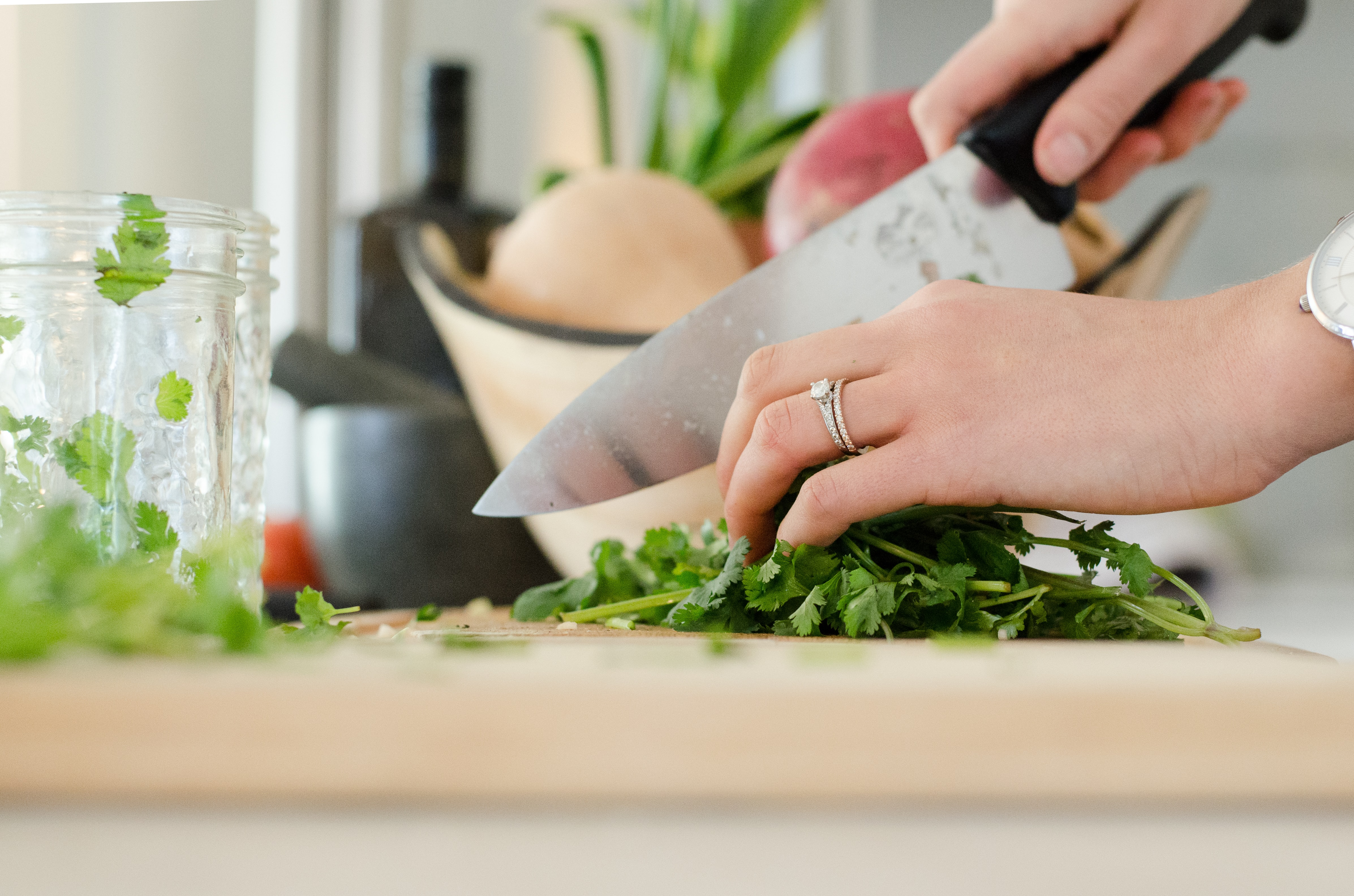 Close up of a woman's hands chopping cilantro on a cutting board.